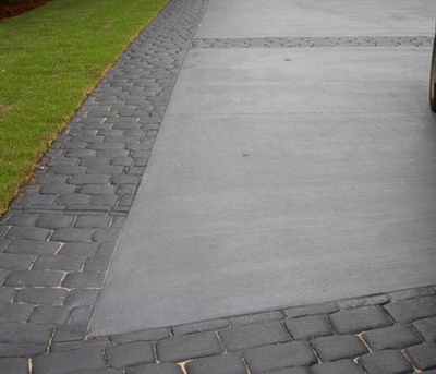 Gray concrete driveway with a gray cobblestone brick design stamped concrete edging.