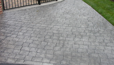 Gray and stamped concrete driveway that resembles an old cobblestone walkway.