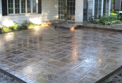 Dark stained and polished stamped concrete patio and step to back door of home.