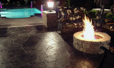 Very dark brown stone style stamped concrete patio with a built in fire pit