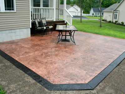 Brown stained stamped concrete patio with a black stained and stamped edge.